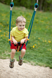cute baby boy playing on swing in spring park