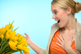Fotografie Surprised woman receive bouquet of yellow tulips