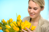 Fotografie Woman looking down at spring yellow tulips