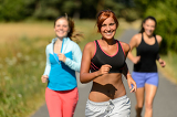 Three friends running outdoors smiling