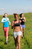 Three girls jogging downhill summer meadow