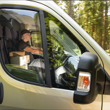 Fotografie Courier man driving car delivering postal package