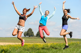 Sporty friends jumping cheerful on sunny meadow