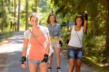 Three women friends roller skating outdoors