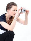 the attractive woman making photo with digital camera on white background