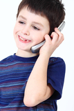 small boy calling from mobile phone to friend on white background