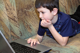 small boy browsing on internet at home