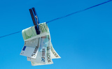 concept of  money hanging on clothesline against blue sky