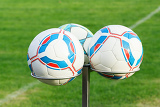 Fényképek three football bals on holders with green grass in background