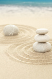balance zen stones in sand with sea in background