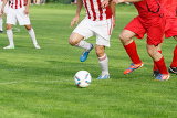 soccer player legs dribbling in a match on green grass