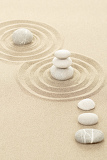 balance of three zen stones in sand