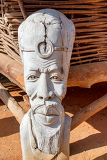 african carved wooden statue in front of dwelling