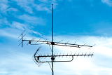 Photo old analog television antenna against blue sky
