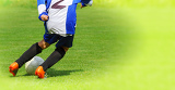 Fotografie young school child soccer player legs dribbling in a match