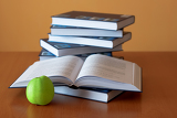Fotografie green apple and opened books on the desk