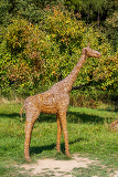 abstract straw giraffe in zoo park with green trees in background