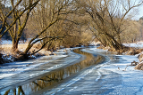sunny day in winter landscape with frozen river