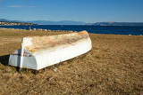 Fotografie old boat stranded on stone beach with blue sky