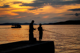 silhouettes of father and his son fishing on the beach at sunset