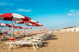 red and white umbrellas and sunlongers on the sandy beach in italy