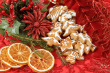 Fotografia christmas background with needles orange slices and gingerbreads on red