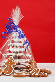 homemade christmas gingerbreads tree with blue ribbon on red background