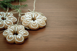 gingerbread cookies with twig hanging over wooden background