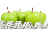 Fotografia measuring tape around a green apples as a symbol of diet on white background