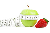 Photo measuring tape wrapped around a green apple and strawberry as a symbol of diet concept