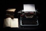 Photo retro typewriter with stack of book and one opened book black background