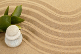 Fotografie background with balance zen stones in sand and green leaves