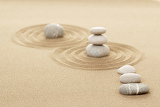 balance of three zen stones in sand with shallow focus