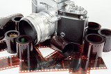 Fotografie analog vintage slr camera and color negative films on white