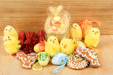 easter decoration gingerbread chicken and painted eggs wooden background
