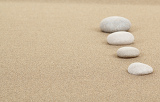 Fotografia four zen stones in sand as background or backdrop