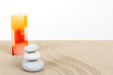 Fotografia balance zen stones and candle in sand on white background