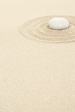 zen stones in soft sand with circles
