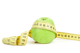 Fotografie green apple and yellow measuring tape isolated on white background