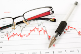 business graph with glasses and pen in the background business collage