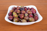 acid purple and green plums blackthorns in bowl on wooden desk