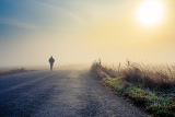 Fotografia a person walk into the misty foggy road in a dramatic mystic sunrise scene with abstract colors