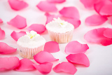 Fotografia cupcakes muffins with white icing on white table with rose petals