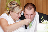 Photo tradition bride feeding her groom with spoon on wedding lunch