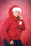 Fényképek joyful pretty woman in red santa claus hat smiling on red background