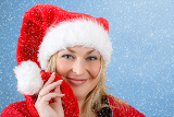 Fényképek joyful pretty woman in red santa claus hat smiling on blue background