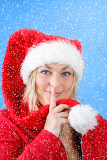 Fotografie joyful pretty woman in red santa claus hat smiling on blue background