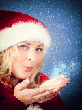 Fényképek joyful pretty woman blowing stars in red santa claus hat on snowy blue background
