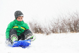 a young boy shows his excitement sledding down a hill in winter