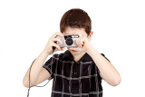 small boy photographing horizontal with digital camera on white background